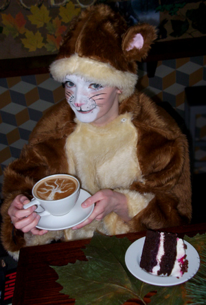 Emily Denison as a dormouse enjoys a slice of cake and Fi Rowntree's coffee art.